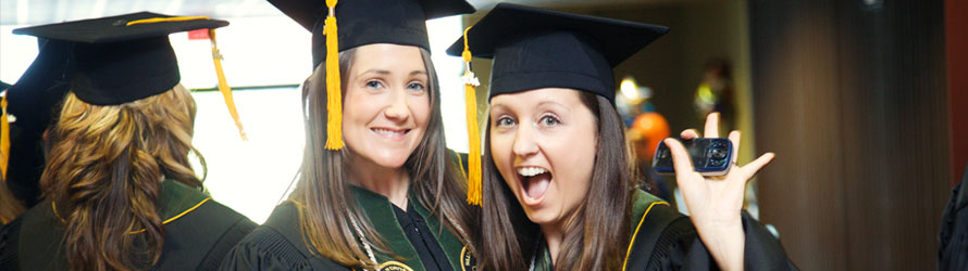 two woman looking excited in graduation caps and gowns