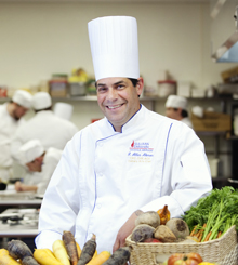 man in chefs uniform with a bunch of vegetables on the table