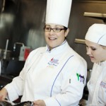 two woman in culinary arts uniforms cooking in the kitchen