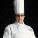 female chef in uniform and hat headshot