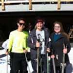 three students posing by the lodge on the ski trip