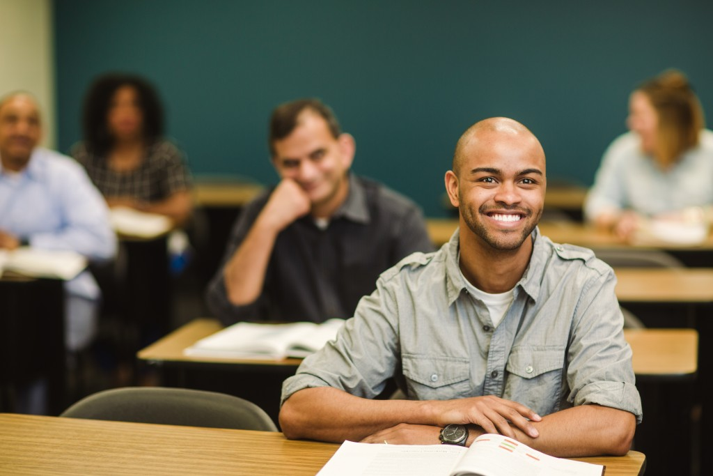 man sitting in a class smiling