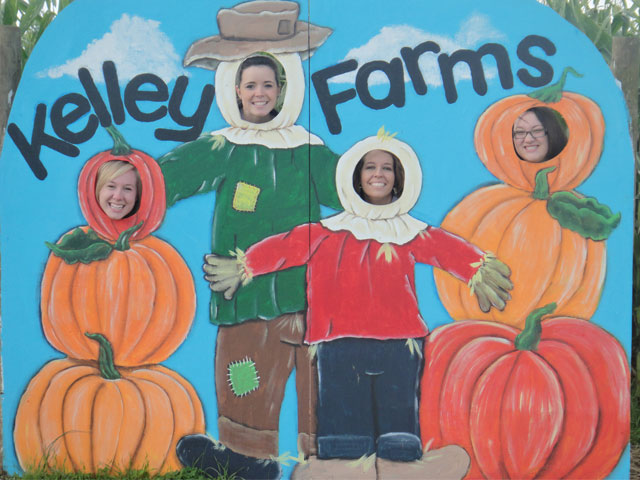people posing with a sign at Kelley farms