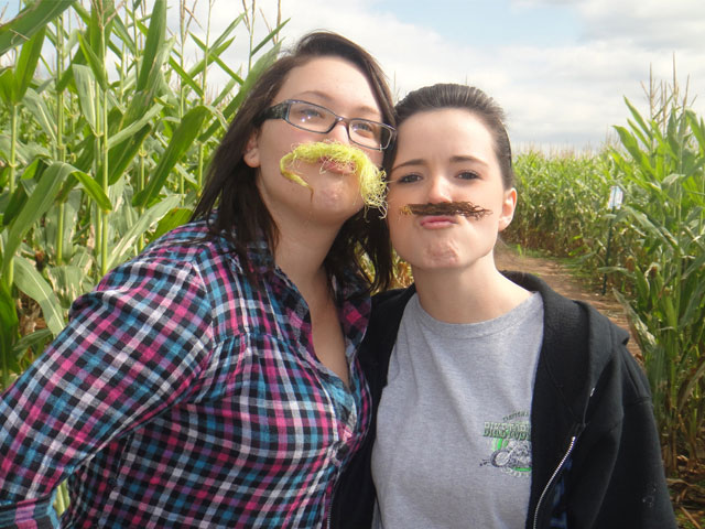 two girls with corn husks as mustaches