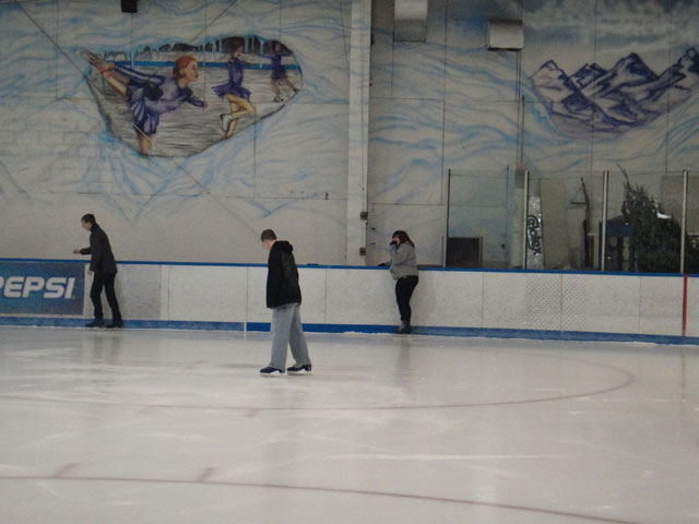 three students ice skating
