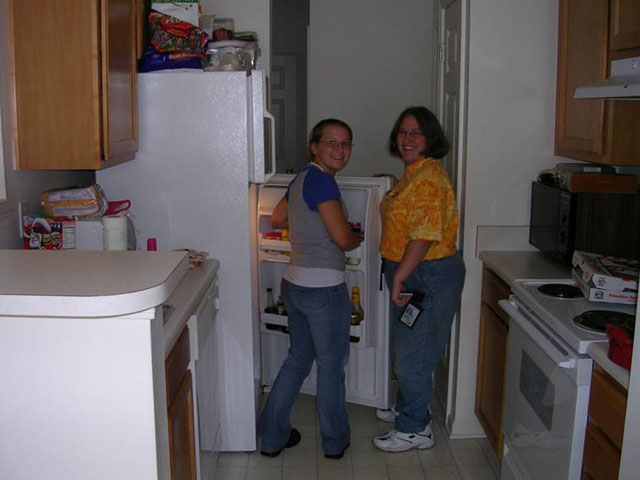 two women standing in their kitchen with the fridge open