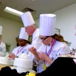 chef teaching culinary students as they decorate cakes