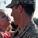 man in military uniform holding his daughter