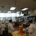 multiple culinary students cooking in a large kitchen