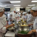 multiple culinary students preparing some vegetables in a large kitchen