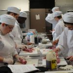 multiple culinary students cutting meet in a kitchen