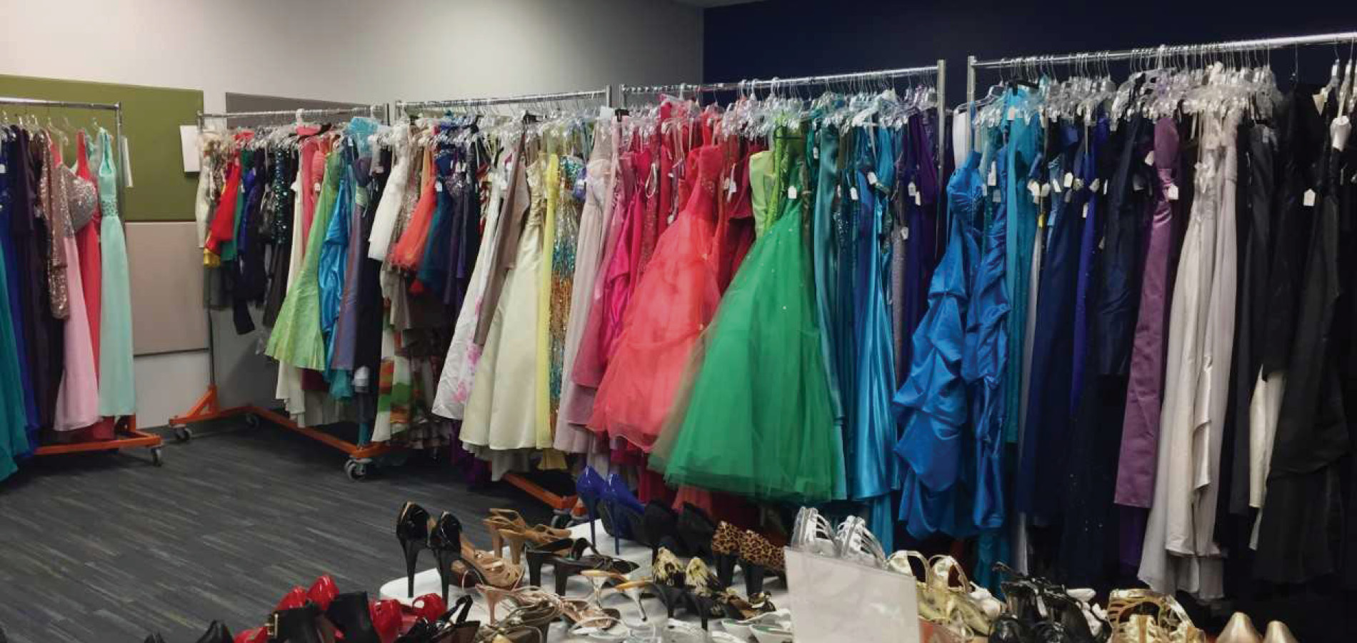 several different color dresses on a clothing rack and lots of high heels on a table