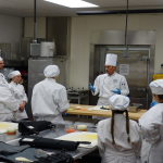 Students listening to head chef.