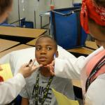 Students at medical camp examining patient.