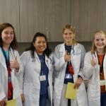 Students at medical camp giving thumbs up.