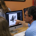 An instructor helping a student in the design camp.